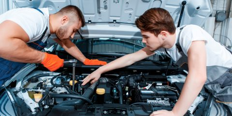 They can fix anything. Two handsome car mechanics in uniform checking the engine under hood in the car service station